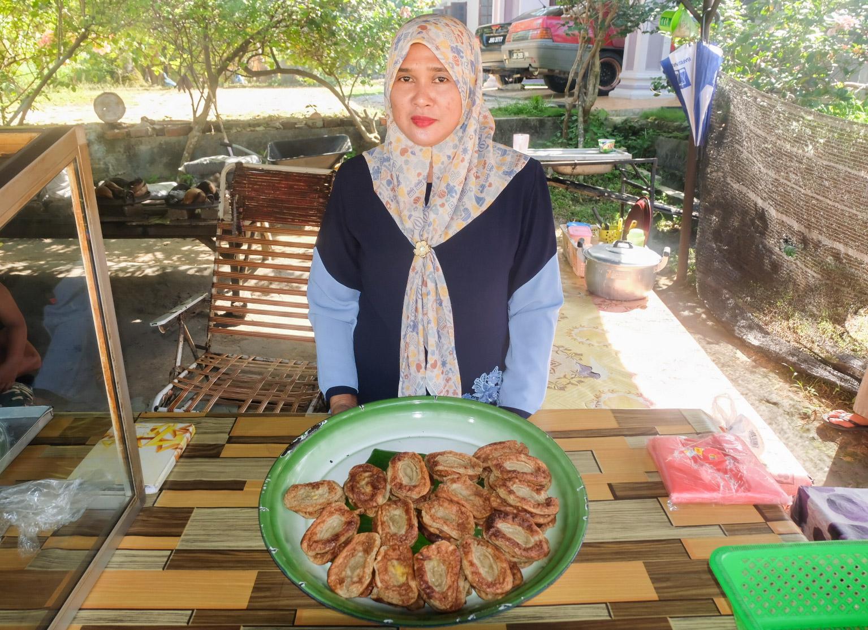 Sarifah Yaacob menunjukkan kuih akok yang telah siap dibakar.