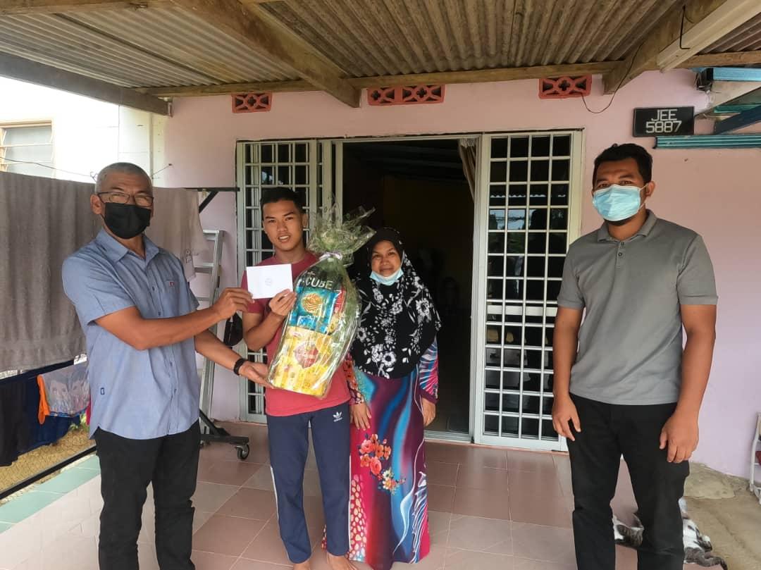 Pegawai Penyelaras DUN Langkap menyampaikan sumbangan hamper dan wang tunai kepada Muhammad Nasrul Idham bin Jusin pelajar cemerlang SMK Sungai Tong