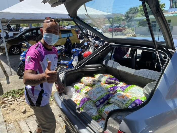 Pengerusi JPKK Tok Kaya, Syed Hussin sedang mengangkut barang keperluan untuk masyarakat Kg. Tok Kaya.