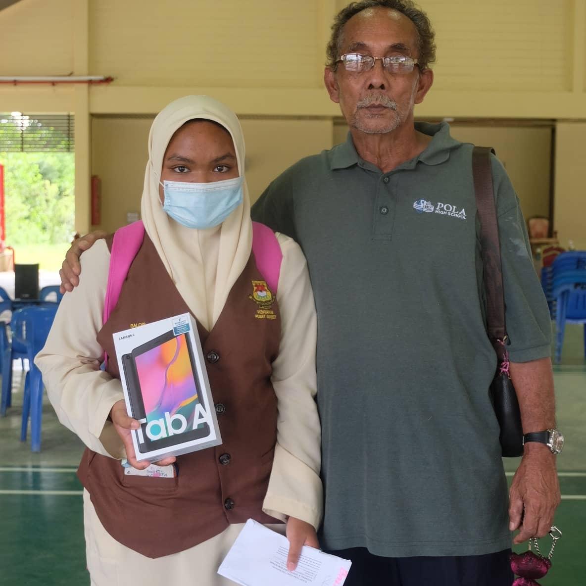 Siti Nur Balqis Mazlan dengan datuknya bersama tablet yang diterima